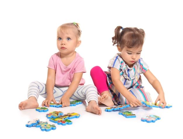 Urocze małe dzieci bawiące się na białym tle