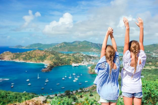 Urocze małe dzieci, ciesząc się widokiem malowniczego angielskiego portu w antigua na morzu karaibskim