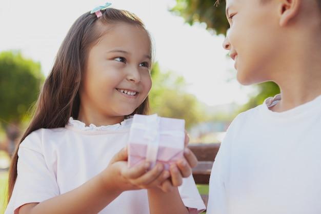 Urocze małe dzieci korzystających z ciepłego słonecznego dnia w parku