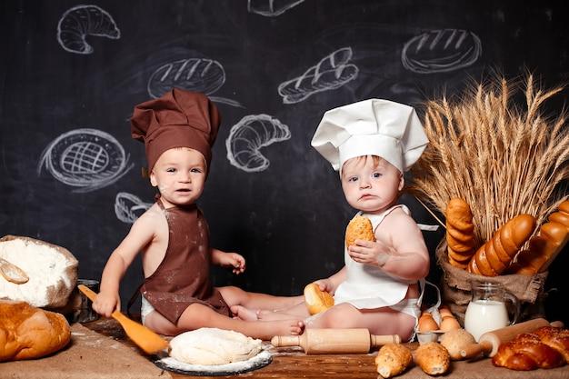 Urocze małe dzieci w fartuchach na stole z chlebem