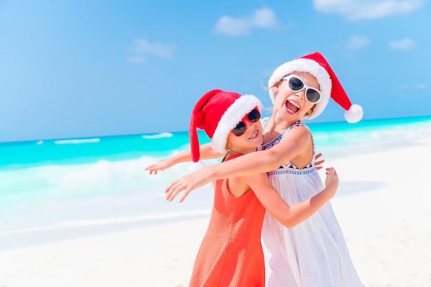 Urocze małe dzieci w santa hat podczas świątecznych wakacji na plaży. nowy rok na plaży