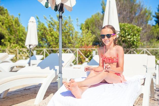 Urocze małe dziecko na leżaku na plaży podczas letnich wakacji