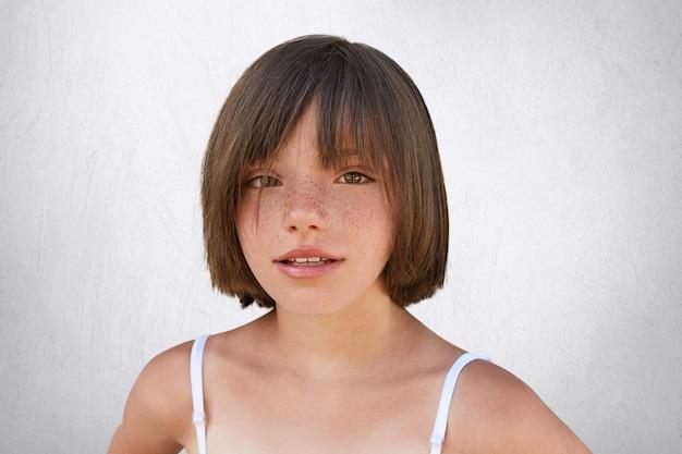 Urocze małe dziecko o brązowych uroczych oczach, piegowatej skórze i cienkich ustach, ze stylową fryzurą, w letnich ubraniach, patrząc prosto w kamerę, gdy pozuje na białym tle.