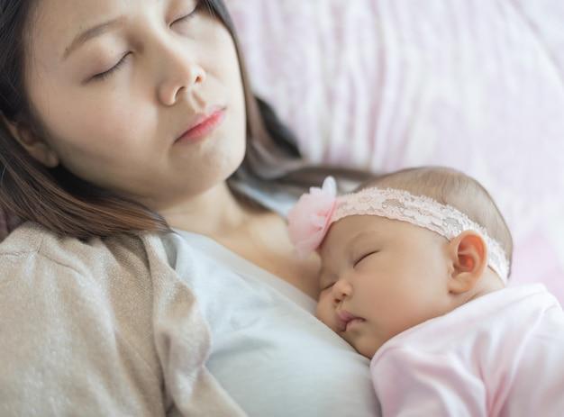 Urocze małe dziecko śpi na piersi matki, matka też śpi