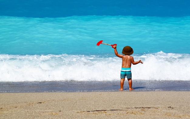 Urocze małe dziecko stojące na piaszczystej plaży i patrzące na falujący ocean
