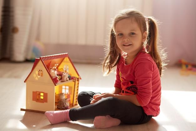 Urocze małe dziecko z dwoma kucykami, dziewczynka w wieku przedszkolnym bawi się domkiem z zabawkami, siedząc na podłodze w słonecznym pokoju, spędzając czas w domu