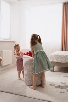 Urocze małe dziewczynki bawiące się w swoim pokoju