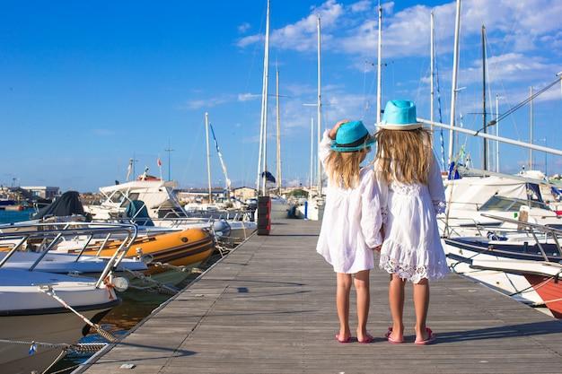 Urocze małe dziewczynki chodzi w porcie w letni dzień