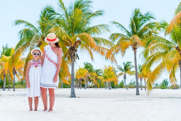 Urocze małe dziewczynki i młode matki na tropikalnej białej plaży