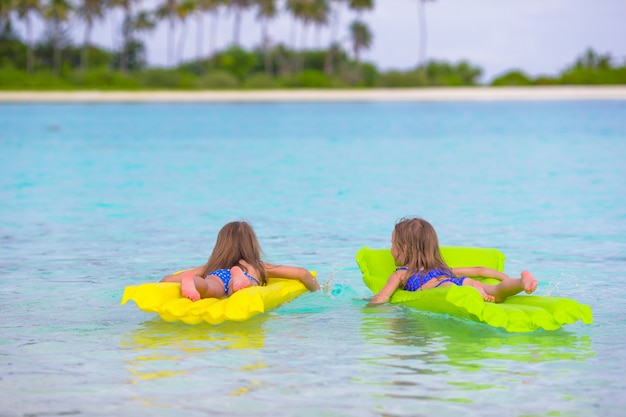 Urocze małe dziewczynki na nadmuchiwanym materacu w morzu podczas letnich wakacji
