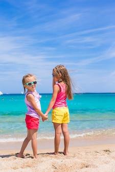 Urocze małe dziewczynki na plaży podczas letnich wakacji