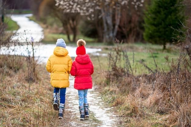 Urocze małe dziewczynki na zewnątrz w lesie na zimę