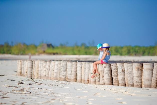 Urocze małe dziewczynki podczas letnich wakacji na białej plaży