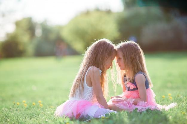 Urocze małe dziewczynki siedzi na trawie na wiosna dniu outdoors