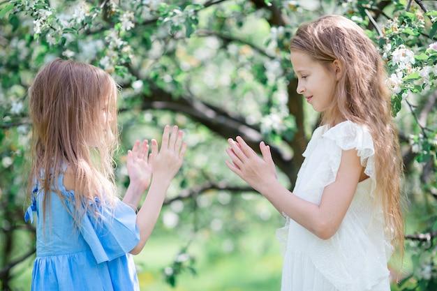 Urocze małe dziewczynki w kwitnącym jabłoń ogródzie na wiosna dniu
