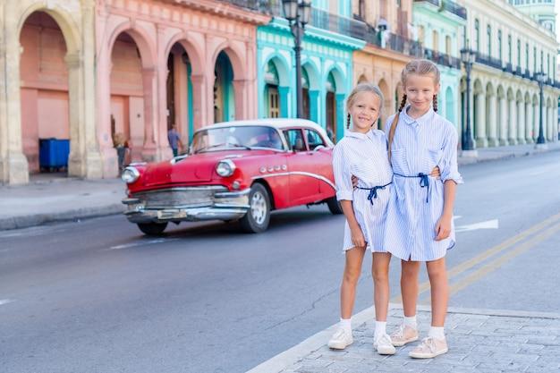 Urocze małe dziewczynki w popularnej okolicy w starej hawanie na kubie. portret dwojga dzieciaków na zewnątrz na ulicy w hawanie