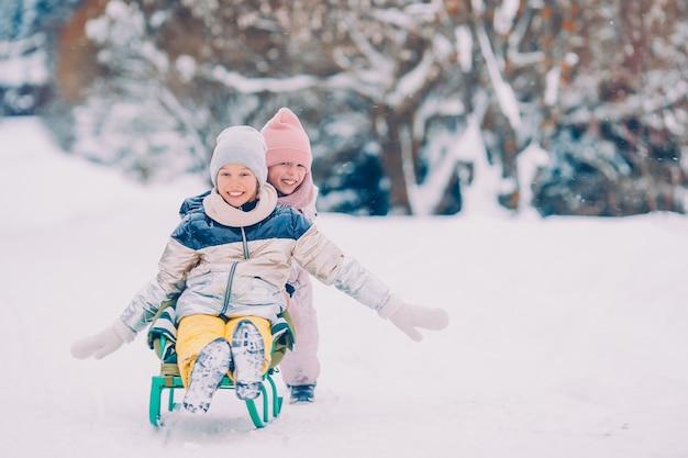 Urocze małe szczęśliwe dziewczyny na sankach w zimowy śnieżny dzień.