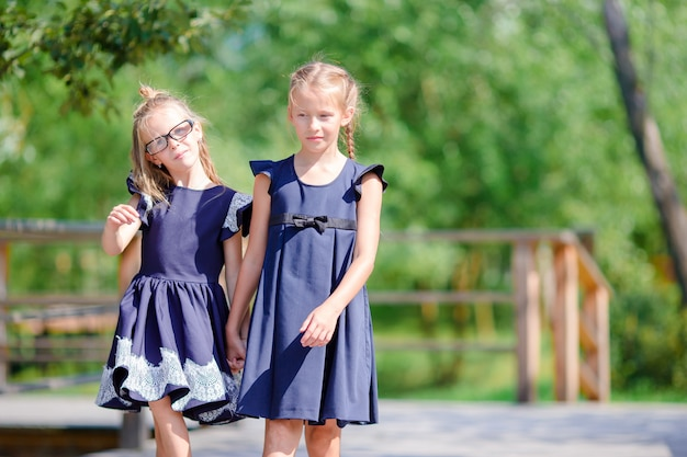 Urocze małe szkolne dziewczyny na zewnątrz jesienią