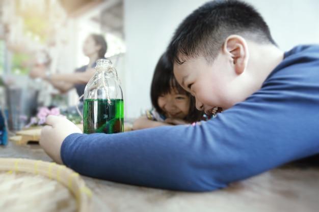 Urocze młode azjatyckie dzieci bawiące się w domu. zajęcia domowe dla dzieci.