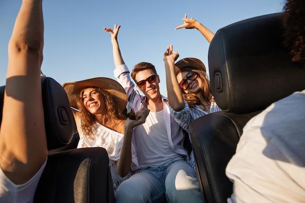 Urocze młode ciemnowłose kobiety w kapeluszach siedzą z młodym mężczyzną w czarnym kabriolecie i trzymają się za ręce.