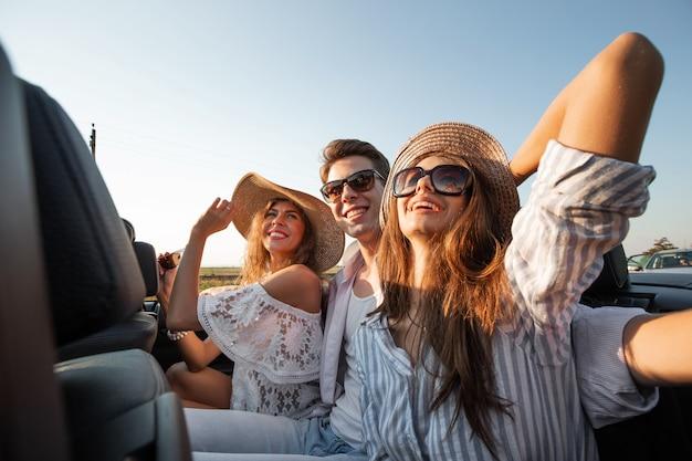 Urocze młode ciemnowłose kobiety w kapeluszach siedzą z młodym mężczyzną w czarnym kabriolecie i uśmiechają się w letni dzień. .