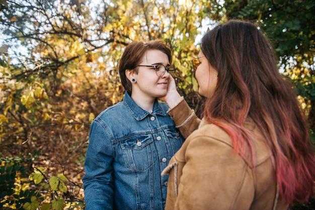 Urocze młode kobiety całujące się delikatnie i kochające się, głaszcząc, dotykając skóry twarzy, ciesząc się romantycznymi chwilami na piknikowej randce na wsi.