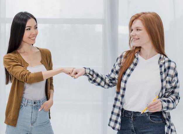 Urocze młode kobiety dotykające pięści