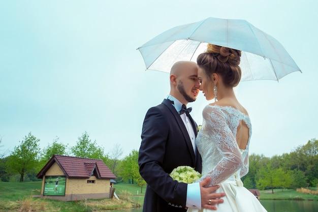 Urocze młode małżeństwo uśmiechając się do siebie pod parasolem
