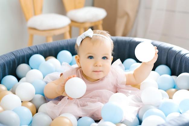 Urocze niebieskookie jednoroczne dziecko w różowej sukience kąpie się w zabawkowym basenie z kolorowymi balonami