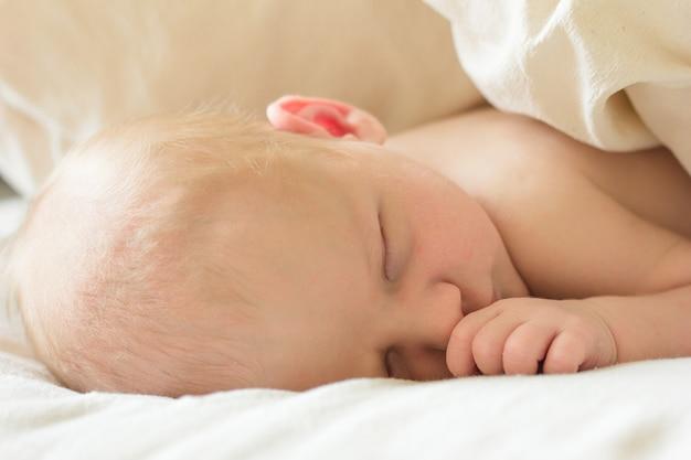 Urocze noworodek śpi w przytulnym pokoju. śliczny szczęśliwy dziecięcy dziecko portret z śpiącą twarzą w łóżku