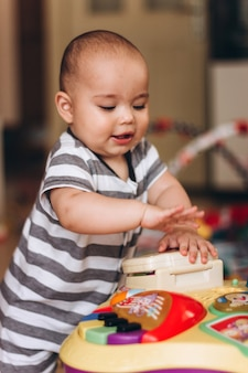 Urocze pucołowate dziecko stoi i bawi się stolikiem muzycznym dla dzieci. wszędzie pełno kolorowych zabawek.