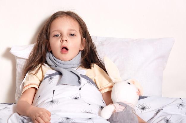 Urocze słodkie dziecko leżące w łóżku z zabawką