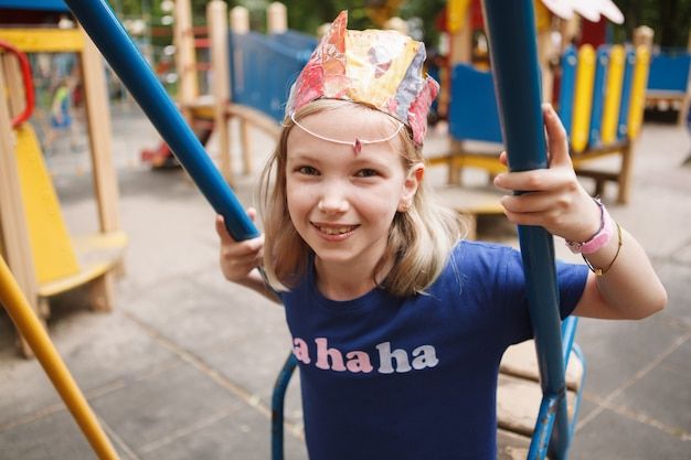 Urocze szczęśliwe dziecko uśmiechnięte, siedzące na huśtawce na placu zabaw