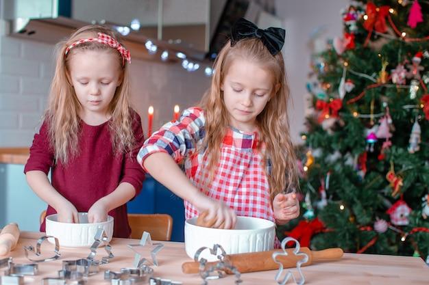 Urocze szczęśliwe małe dziewczynki piec bożenarodzeniowych piernikowych ciastka w xmas wigilii