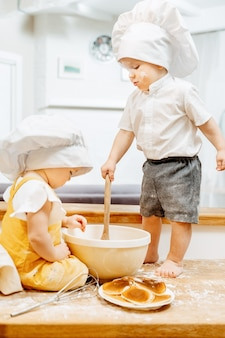 Urocze, umorusane kaukaskie dzieci gotują w weekend ciasto i naleśniki, siedząc na stole w kuchni. pojęcie niespokojnych dzieci badaczy. praca domowa dla dzieci w wieku przedszkolnym