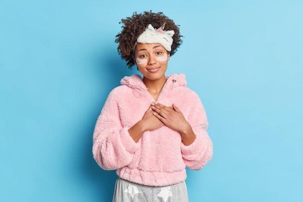 Urocze, uśmiechnięte kręcone włosy trzyma dłonie przyciśnięte do serca sprawia, że gest wdzięczności jest przyjemny, gdy kładzie się do łóżka ubrany w bieliznę nocną, nakłada plastry kolagenowe w celu zmniejszenia zmarszczek pozuje w pomieszczeniach