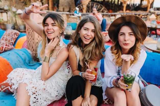 Urocze, uśmiechnięte siostry spędzają czas w restauracji na świeżym powietrzu, pozując ze znakami pocałunku pokoju i powietrza