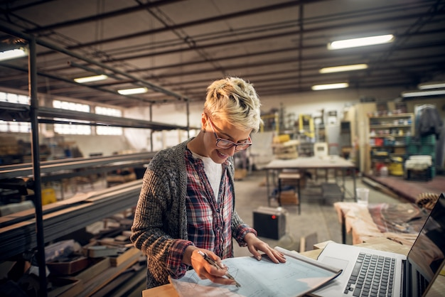 Urocze, uśmiechnięte, zmotywowane inżynierki o krótkich włosach z okularami pracującymi z planami i laptopem w warsztacie