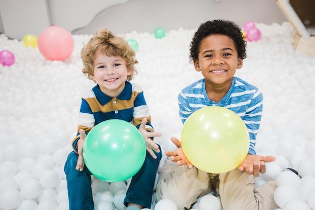 Urocze, wesołe, międzykulturowe chłopcy w pasiastych koszulkach bawiących się zielonymi i żółtymi balonami w pokoju dziecięcym lub przedszkolu