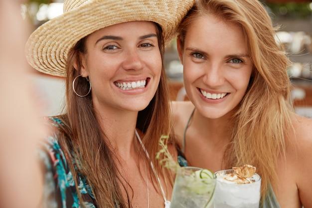 Urocze, wesołe suczki z szerokimi uśmiechami, pozują do selfie, piją zimne orzeźwiające koktajle. zrelaksowane blogerki odtwarzają się w tropikalnym kraju. pozytywne młode kobiety robią sobie zdjęcia