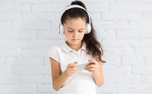 Uroczej małej dziewczynki słuchająca muzyka z słuchawkami