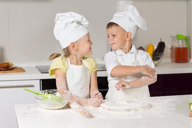 Uroczi mali kucharze bardzo szczęśliwi bawią się w kuchni