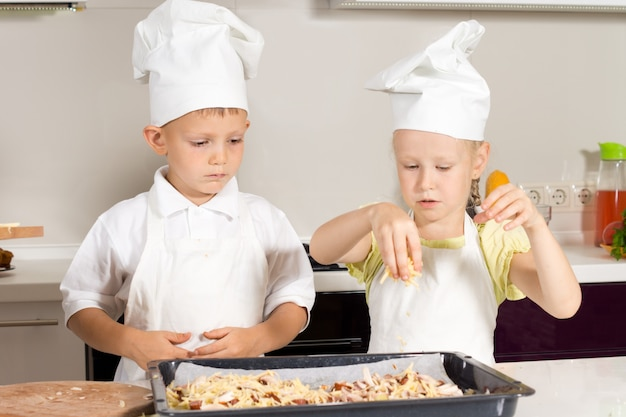 Uroczi mali kucharze poważnie kładą ser na pizzy w kuchni