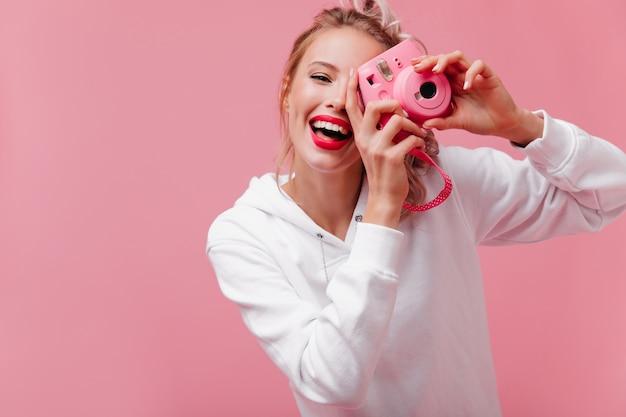 Uroczo uśmiechnięta kobieta z blond włosami trzymając przód