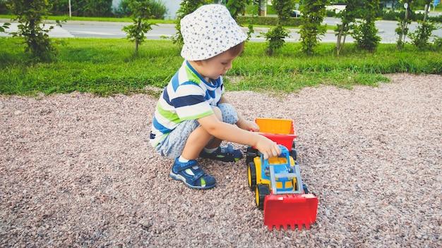 Uroczy 3-letni chłopiec bawiący się piaskiem, a ty ciężarówka i przyczepa w parku?