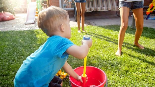 Uroczy 3-letni chłopiec rozpryskujący wodę z plastikowego pistoletu zabawkowego na podwórku domu. dzieci bawiące się i bawiące na świeżym powietrzu latem