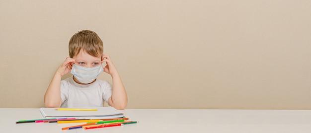 Uroczy 4-letni chłopiec w masce medycznej siedzi w domu w kwarantannie. rozrywka dla dziecka podczas kwarantanny - rysunek.
