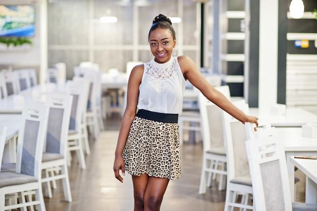 Uroczy african american kobieta w spódnicy lamparta pozowanie w restauracji.