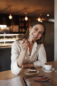 Uroczy biznes kobieta je pyszny deser i uśmiechnięty.
