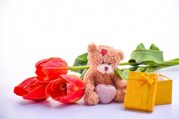 Uroczy brązowy miś, bukiet czerwonych tulipanów, pudełko prezentowe,